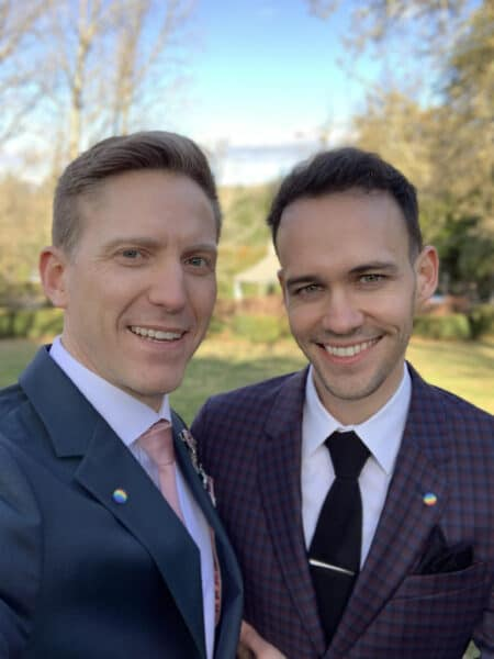 Brad and his fiancé Jamie stand outdoors on a sunny day and smile for a photo. They are both wearing jackets and ties with rainbow pride buttons on the lapels.